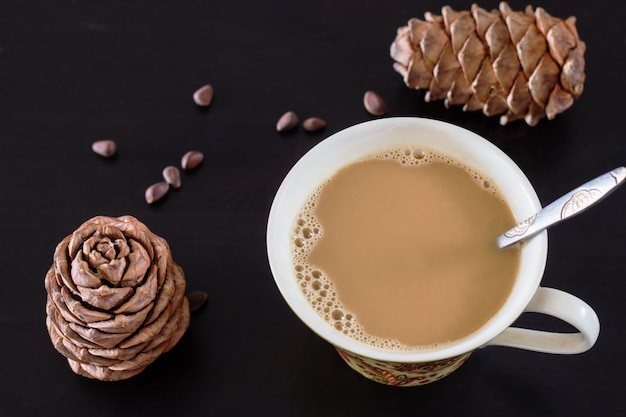 松の実と杉ビーガンミルクのコーヒーまたはミルクティーチャイ。黒い木製の背景とシベリア杉松の円錐形。上面図。セレクティブフォーカス。 Premium写真