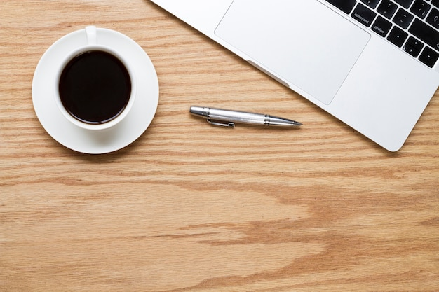 Coffee next to pen and laptop Free Photo