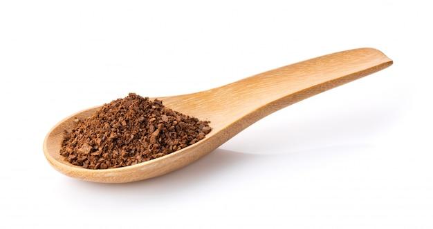 Кофейный порошок в деревянной ложкой на белом Premium Фотографии
