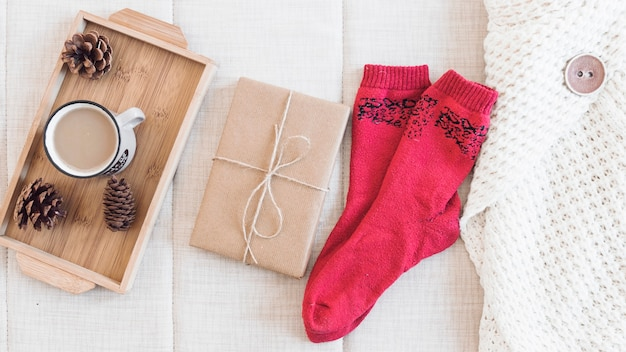 Coffee and present near socks and sweater Free Photo
