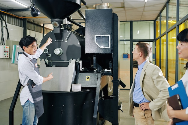 Coffee roastery worker showing new machine to investor and talking about its benefits Premium Photo