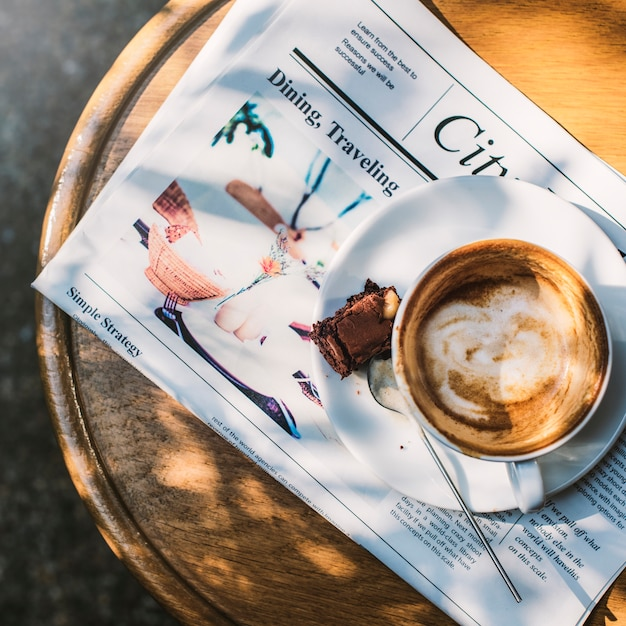 Coffee shop cafe latte cappuccino newspaper brownie concept Free Photo