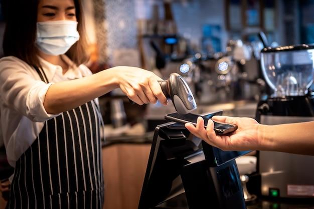Владелец кофейни, азиатка. прием платежей от клиентов с помощью сканера штрих-кода. с мобильным приложением клиента, людям и новой нормальной концепции. Premium Фотографии