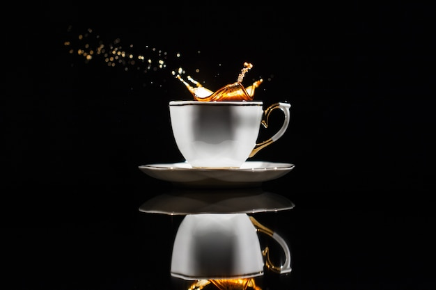 Coffee splashes in white cup on black background Free Photo