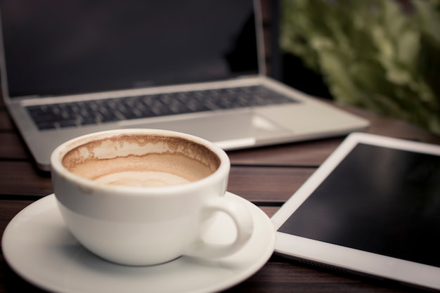Coffee on table with laptop working in cafe, relax and free time concept Premium Photo