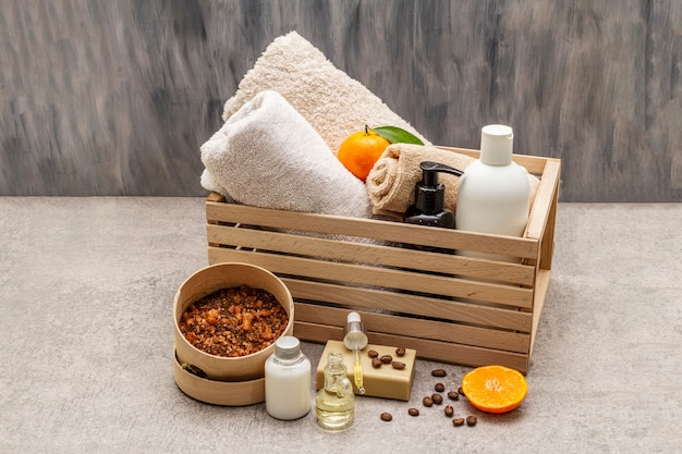 Coffee and tangerine spa concept. towels, oil, scrub, soap, lotion. natural ingredient, wooden box. Premium Photo