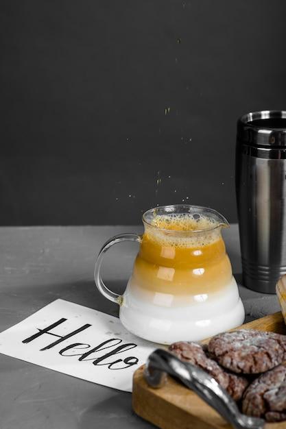コーヒー、長い注ぎ口のあるティーポット、お菓子、そしてこんにちはの碑文が書かれたカード。 Premium写真
