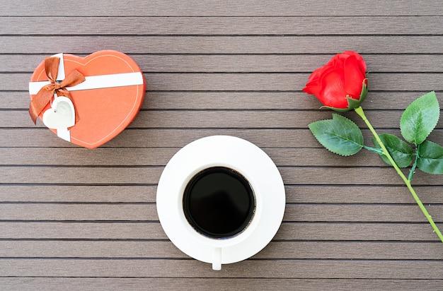 Кофе тайм с чашкой кофе, красная роза Premium Фотографии