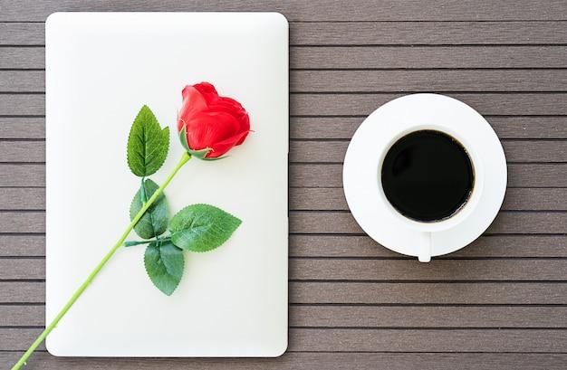 Кофе тайм с ноутбуком, чашка кофе, красная роза Premium Фотографии