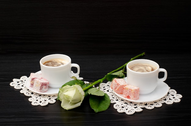 Coffee for two with oriental sweets, a white rose on a black Premium Photo