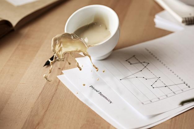 Caffè in tazza bianca che si rovescia sulla tavola di mattina alla tavola dell'ufficio Foto Gratuite