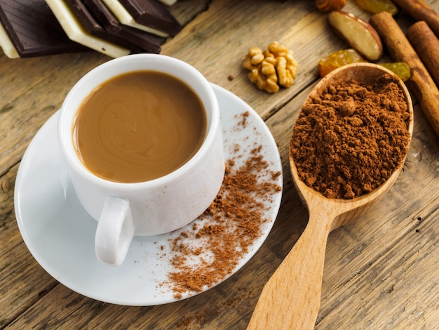 Coffee in a white cup, sweets and scattered cinnamon on a wooden table Premium Photo