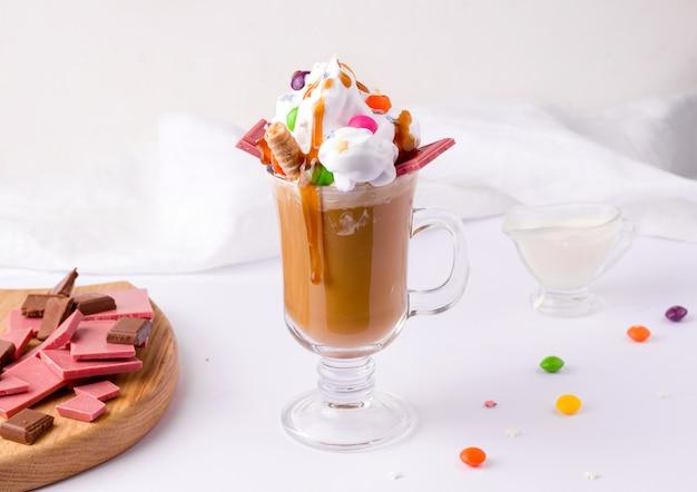お菓子と白い背景の上のチョコレートで飾られたクリームとキャラメルのコーヒー Premium写真