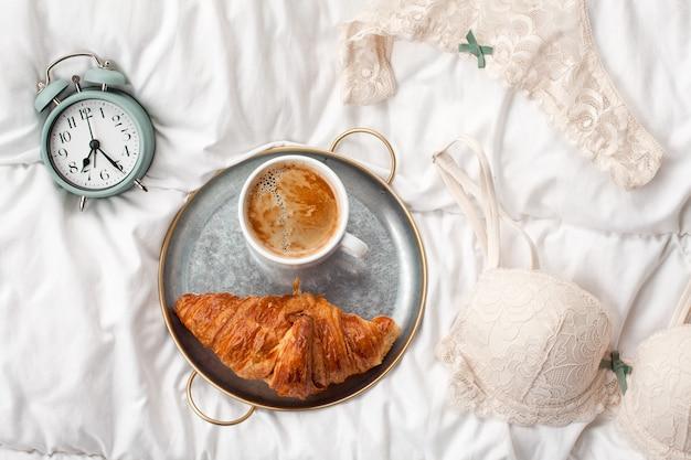 Coffee with croissant, alarm clock, girls underwear Premium Photo