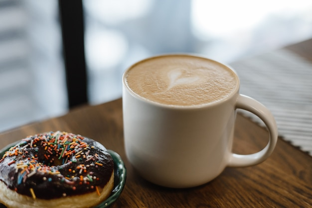 Coffee with a drawn heart and milk on a wooden table in a coffee shop. pink donut with scattering on the table next to the coffee Premium Photo