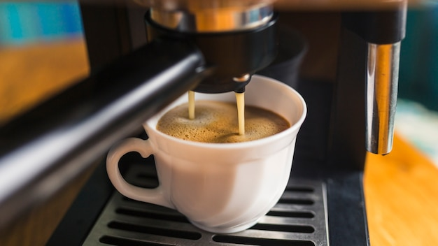 Coffee withfrothing pouring from espresso machine Free Photo