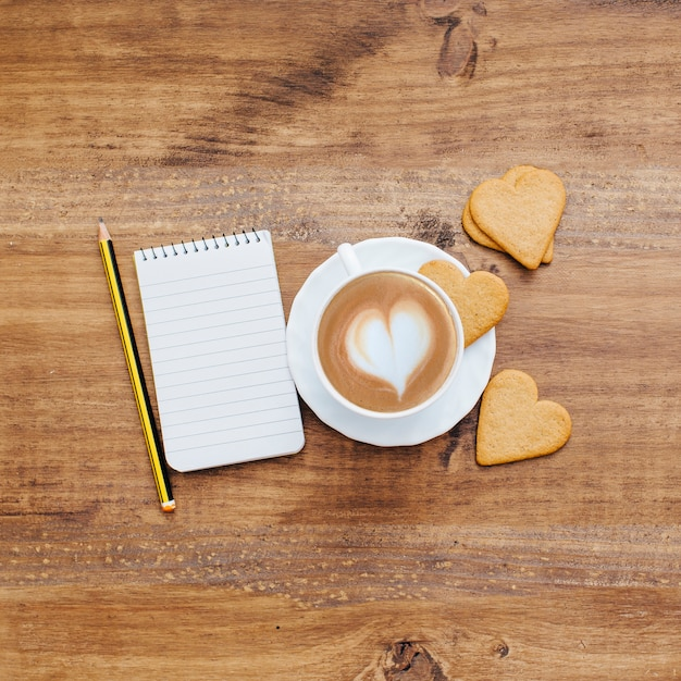 Coffee with heart biscuits and notebook Free Photo