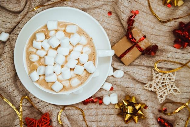 ギフトや休日の弓とニット生地の背景にマシュマロとコーヒー Premium写真