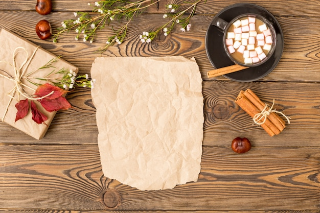 Coffee with milk and marshmallow, gift leaves cinnamon sticks and chestnuts on wooden background. Premium Photo