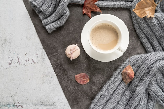 Coffee with milk and warm sweater on shabby surface Free Photo