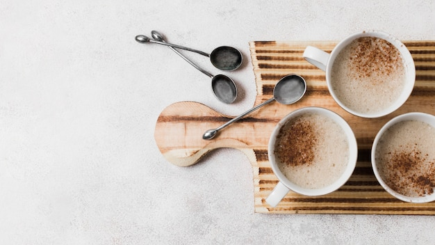 Coffee with milk on wooden board with spoons Free Photo