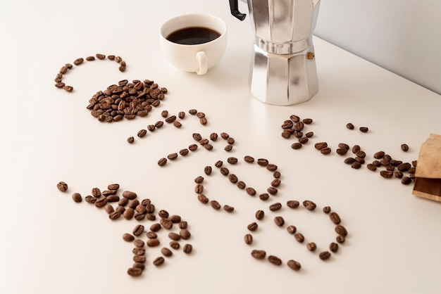 Coffee written with coffee beans on white table Free Photo