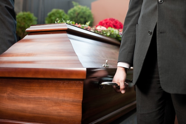 Coffin bearer carrying casket at funeral Premium Photo
