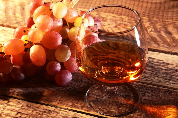 Cognac or brandy in a glass and fresh grapes, still life in rustic style, vintage wooden background, selective focus. Premium Photo