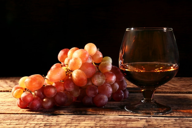Cognac or brandy in a glass and fresh grapes, still life in rustic style Premium Photo