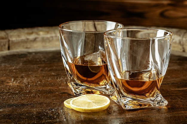 Cognac in glasses with lemon pieces over wooden table Premium Photo