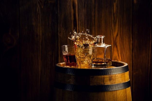 Cognac in glasses, in a wooden barrel cellar splash of alcohol in a glass Premium Photo