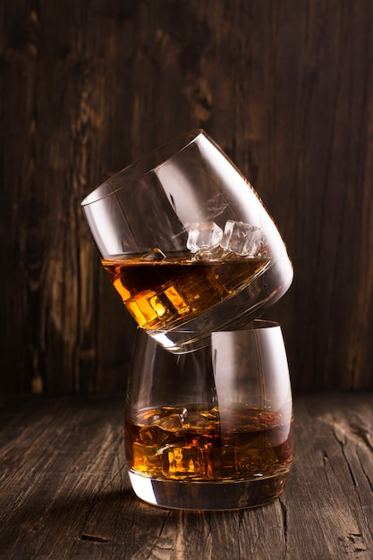 Cognac in glasses over wooden table Premium Photo