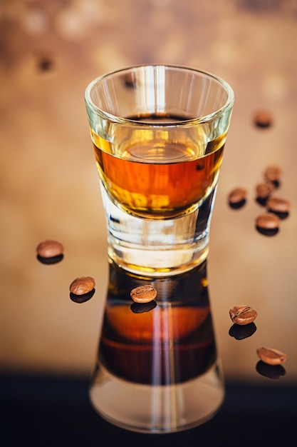 Коньяк или ликер, кофейные зерна и специи на стеклянном столе Premium Фотографии