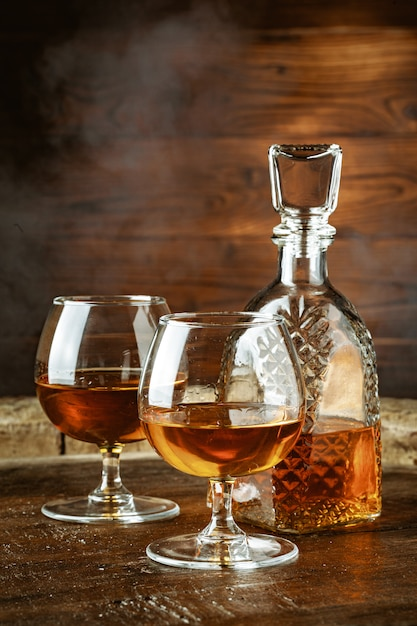 Cognac or whiskey in glasses on rustic backgrpund Premium Photo