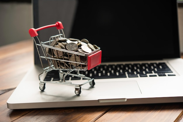 Coin in mini shopping cart on table for work and laptop for work to shopping online concept Premium Photo