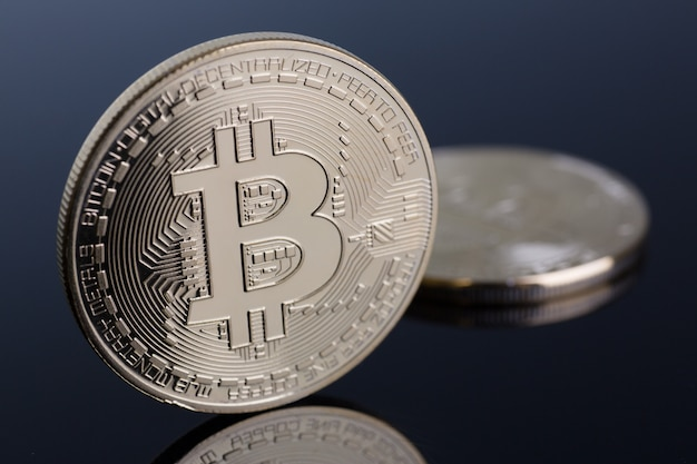Монета криптовалюты bitcoin на серо-голубой предпосылке с отражением подчиняет пирамиду обмена золота на деньгах в связи с крупным планом роста или падения обменного курса. Premium Фотографии