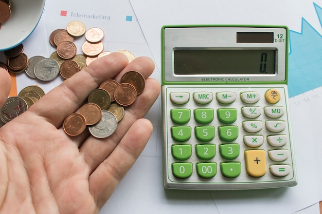 Coin On Male Hand And Calculator On Graph Paper Photo Premium Download