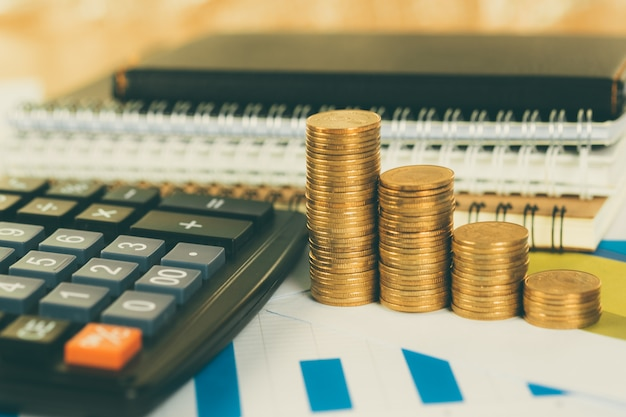 Coin stack and financial graph paper sheet with calculator on working table, business planning vision and finance analysis concept. Premium Photo