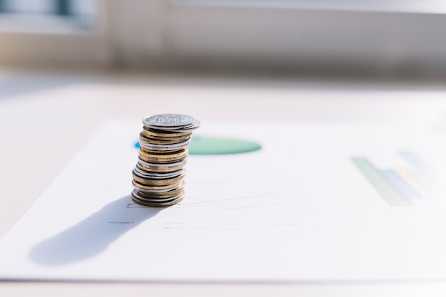 Coin stack on graph over table Free Photo