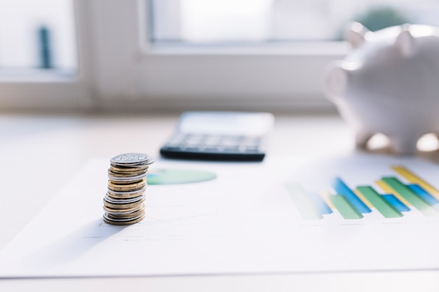 Coin stack on graph with calculator and piggybank over table Free Photo