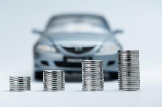 Coin stacks in front of car Free Photo