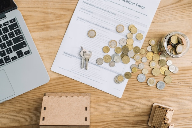 Coins and mortgage application near laptop Free Photo