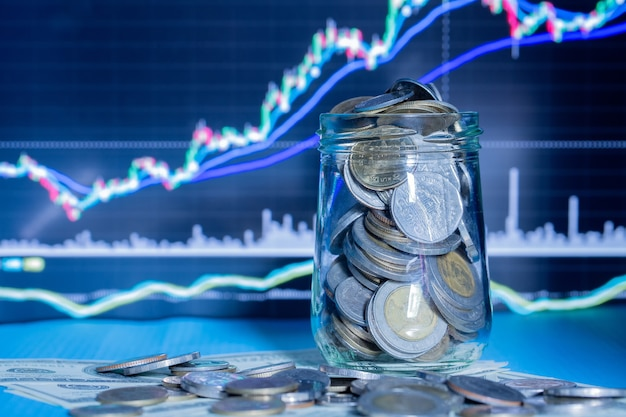 Coins in bottles with trading graph Free Photo