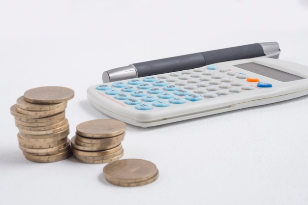Coins next to calculator and pen Free Photo
