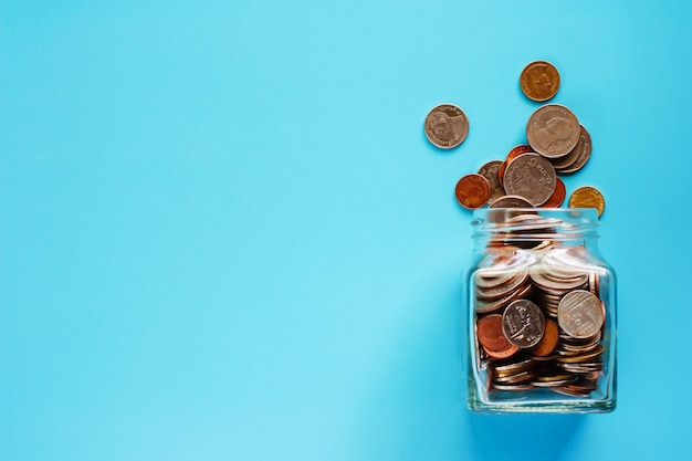 Coins in glass jar and outside, thai currency money on blue background Premium Photo