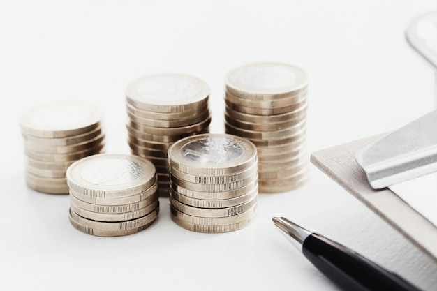 Coins and pen on wooden table Free Photo