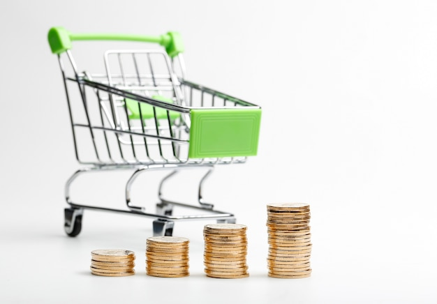 Coins pile and shopping cart on a white background Free Photo
