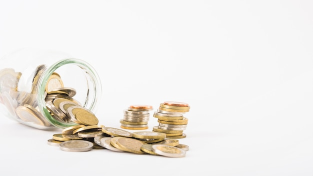 Coins scattered from glass jar Free Photo