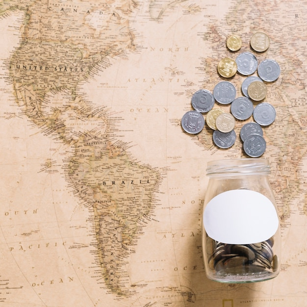 Coins spilling from jar over the world map Free Photo