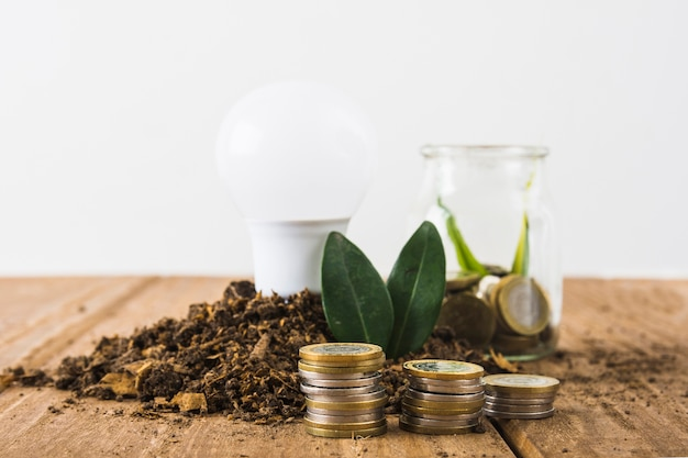 Coins stack with light bulb and jar Free Photo